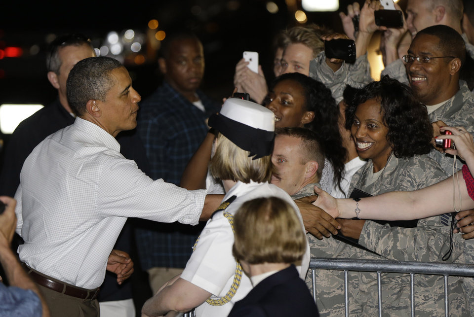 President Barack Obama greets base visitors and personnel before boarding Air Force One to return to Washington, at Honolulu Joint Base Pearl Harbor-Hickam in Honolulu, after spending Christmas with his family in Hawaii, Wednesday, Dec. 26, 2012. (AP Photo/Gerald Herbert)
