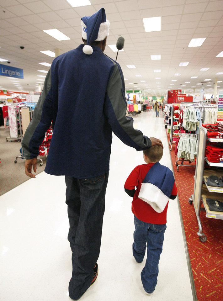 Kevin Durant helps Jacob Franks shop during a shopping spree at Target on Tuesday. Franks' family was one of 10 selected to receive $1,000 donated by Thunder players, coaches and staff. Photo BY BRYAN TERRY, THE OKLAHOMAN