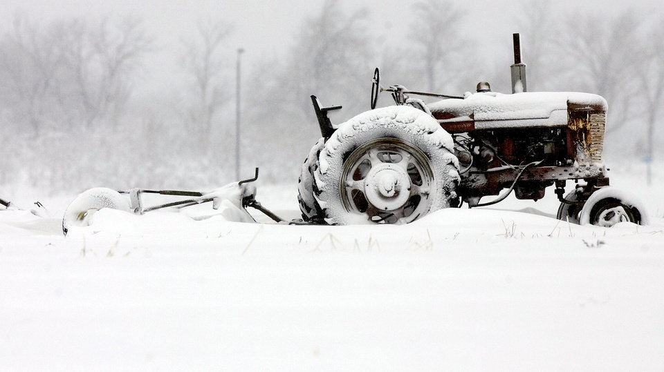 A tractor sits in a snow-covered field in western Lenexa, Kan, on Sunday, March 24, 2013. A storm that dumped up to 15 inches of snow on parts of Colorado and Kansas is making its way east, with winter storm warnings and advisories issued for today and tomorrow as far east as Pennsylvania. (AP Photo/The Kansas City Star, Chris Ochsner)