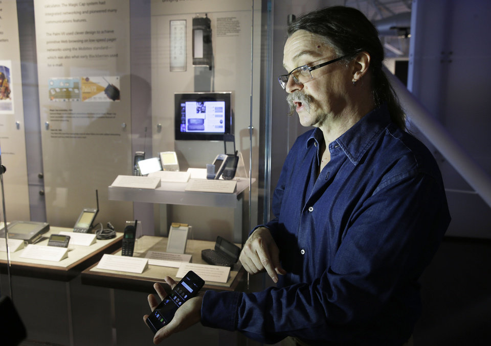 "Photo - In this photo taken Wednesday, July 30, 2014, Silicon Valley pioneer and Silent Circle co-founder Jon Callas shows off his Blackphone with encryption apps on it while standing by a mobile phone display at the Computer History Museum in Mountain View, Calif.  Revelations about the NSA's electronic eavesdropping capabilities, with targets reported to include Chancellor Angela Merkel, have sparked anger in Germany, and a boom in encryption services that make it hard for the most sophisticated spies to read emails, listen to calls or comb through texts. ""Snowden's leaks were a real boon for us,"" said Callas, whose company sells an encryption app which allows users to talk and text in private. Although Silent Circle doesn't provide specific numbers, Callas said they saw a ""huge increase"" in subscriptions to their private phone and text service after a series of disclosures from former intelligence contractor Edward Snowden last year, and a spike in Germany after two reported cases of suspected U.S. spying there earlier this year. (AP Photo/Eric Risberg)"