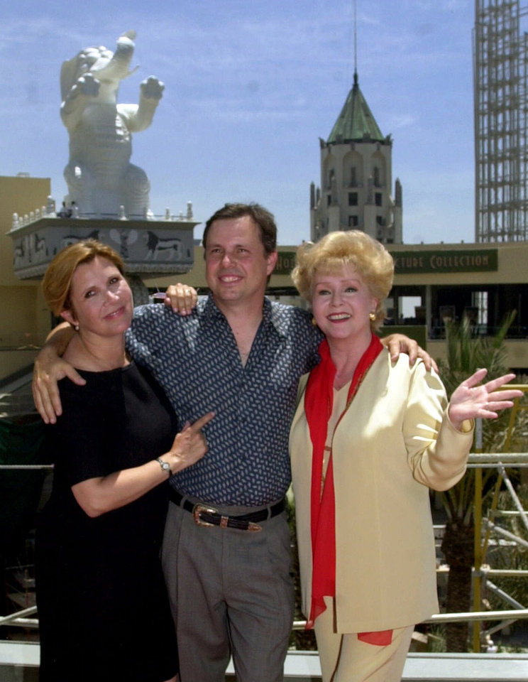 Photo - Actress Debbie Reynolds, right, poses with her children, actress Carrie Fisher, left, and Todd Fisher, during a groundbreaking ceremony at the site of the new Hollywood Motion Picture Museum, Tuesday, June 19, 2001, in Los Angeles. (AP Photo/Nick Ut)