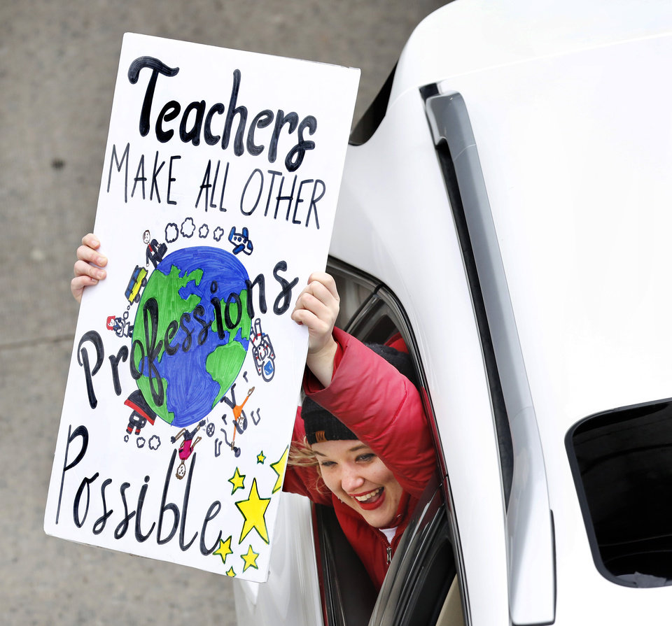 Photo - A passenger in a vehicle traveling on NE 23 Street shouts her support and shows her sign to striking teachers standing on an overpass on the north side of the Capitol. Teachers from throughout the state converged at the Capitol to bring their concerns about education funding to the attention of legislators and state officials during the first day of a statewide public schools teacher walkout  on Monday, April 2, 2018. Photo by Jim Beckel, The Oklahoman