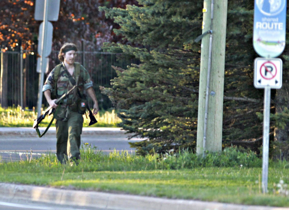 Photo - A heavily armed man that police have identified as Justin Bourque walks on Hildegard Drive in Moncton, New Brunswick, on Wednesday, June 4, 2014, after several shots were fired in the area. The man, suspected of killing three Royal Canadian Mounted Police officers, was spotted three times Thursday but has so far eluded a massive manhunt, police said. (AP Photo/The Canadian Press, Moncton Times & Transcript, telegraphjournal.com, Viktor Pivovarov)