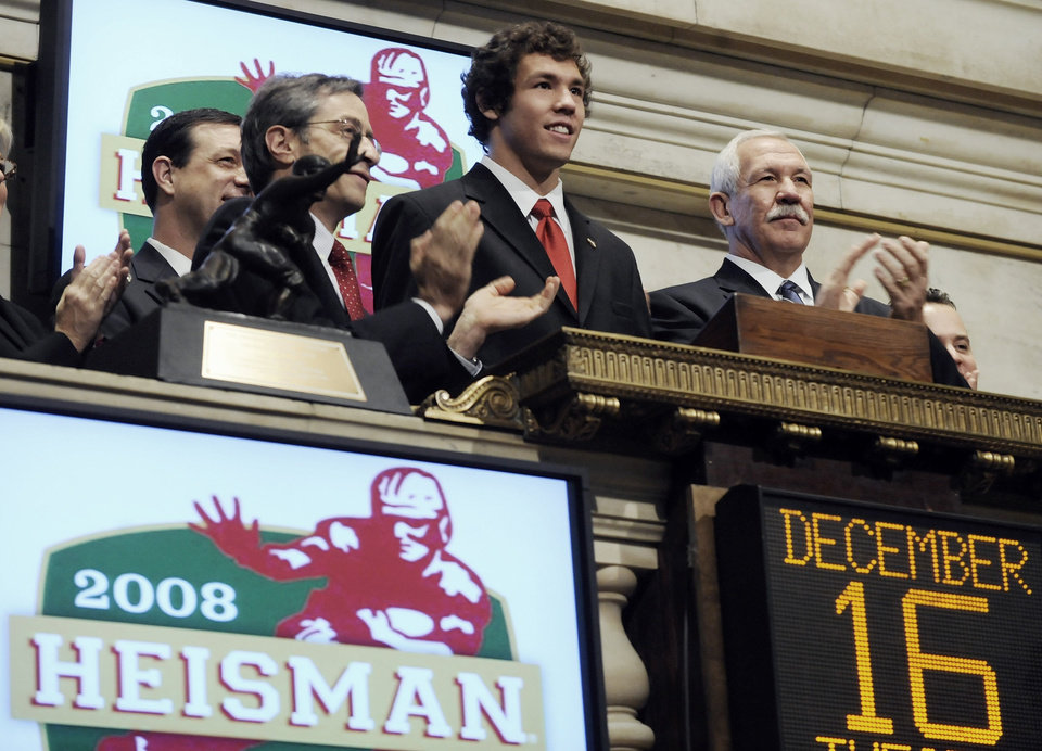 Photo - Sam Bradford, center, the 2008 Heisman Trophy winner from the University of Oklahoma (OU), is applauded as he rings the New York Stock Exchange opening bell Tuesday, Dec. 16, 2008. At left is NYSE Executive Vice President and Chief Operating Officer Lawrence Leibowitz and Bradford's father, Kent Bradford, is at right. (AP Photo) ORG XMIT: NYRD103