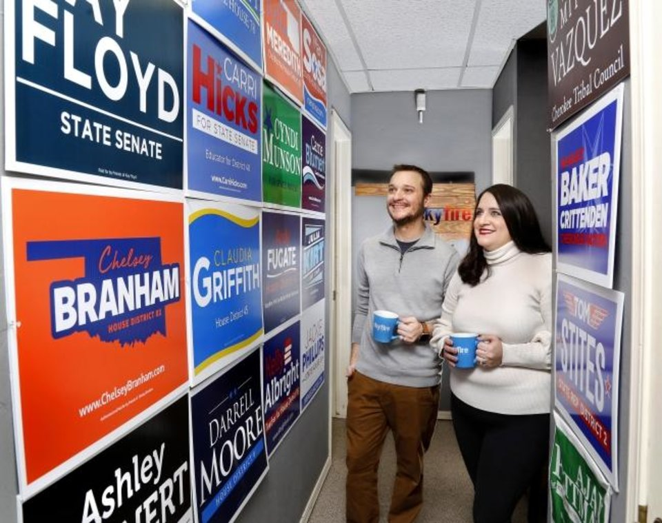 Photo - Joe Hartman and Cassi Peters are co-owners of Skyfire Media. They are shown in an office  hallway covered with political signs from various campaigns they have been closely involved in.  Their business is located just north of  downtown near NW 17 and Shartel. They were photographed on Friday, Feb. 15, 2019. Photo by Jim Beckel, The Oklahoman.