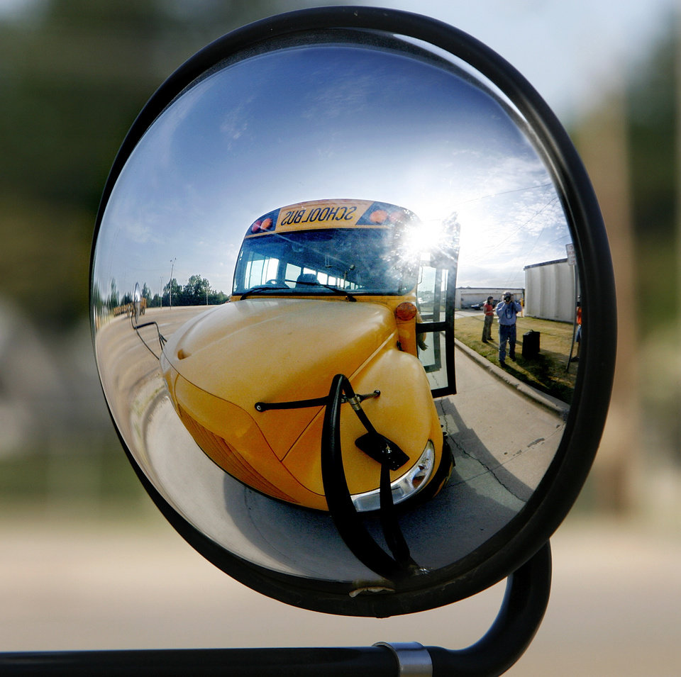 Photo - A school bus is reflected in the bus' mirror at the school's transportation center Thursday,  Aug. 7, 2008.   BY JIM BECKEL, THE OKLAHOMAN ORG XMIT: KOD