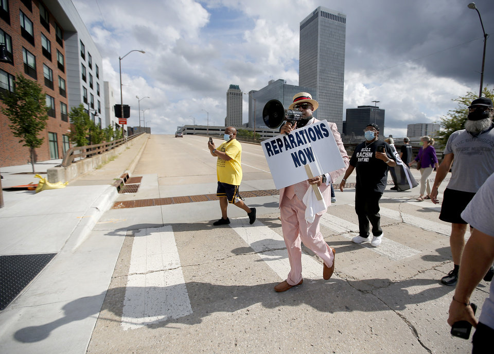 Photo - The Rev. Robert Turner and supporters march to the Vernon A.M.E Church in the Greenwood district in Tulsa, Okla., Wednesday, July 29, 2020. Turner has protested for reparations for victims of the 1921 Tulsa Race Massacre each Wednesday at Tulsa City Hall. Photo by Sarah Phipps, The Oklahoman