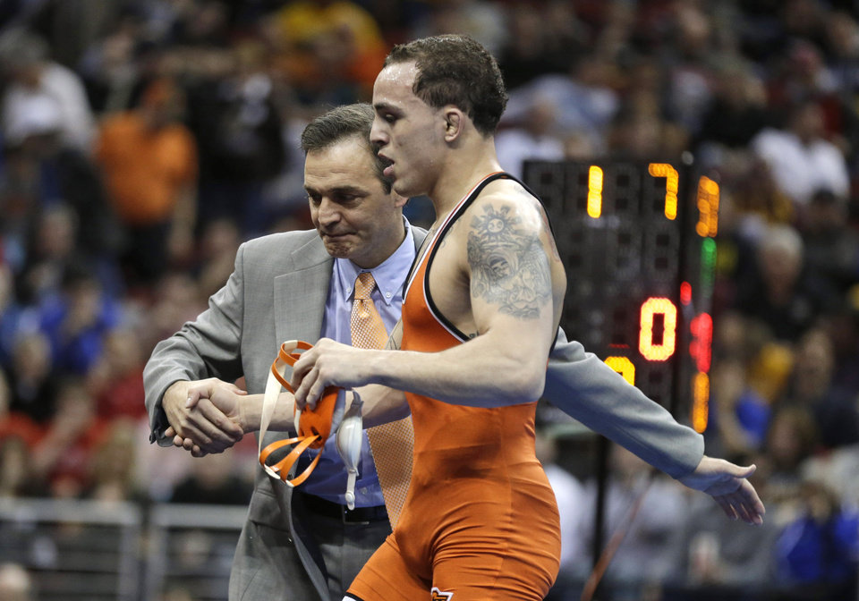 Photo - Oklahoma State's Jordan Oliver received congratulations from coach John Smith after Oliver defeated Boise Stateís Jason Chamberlain in the 149-pound title match at the NCAA Division I wrestling championships, Saturday, March 23, 2013, in Des Moines, Iowa. (AP Photo/Charlie Neibergall)