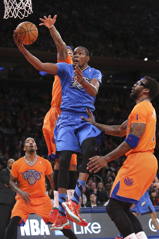 Photo - Oklahoma City Thunder forward Kevin Durant (35) shoots against New York Knicks forward Kenyon Martin, center, as guard J.R. Smith, left, and forward Amare Stoudemire (1) watch during the second half of an NBA basketball game at Madison Square Garden, Wednesday, Dec. 25, 2013, in New York. The Thunder won 123-94. (AP Photo/John Minchillo)