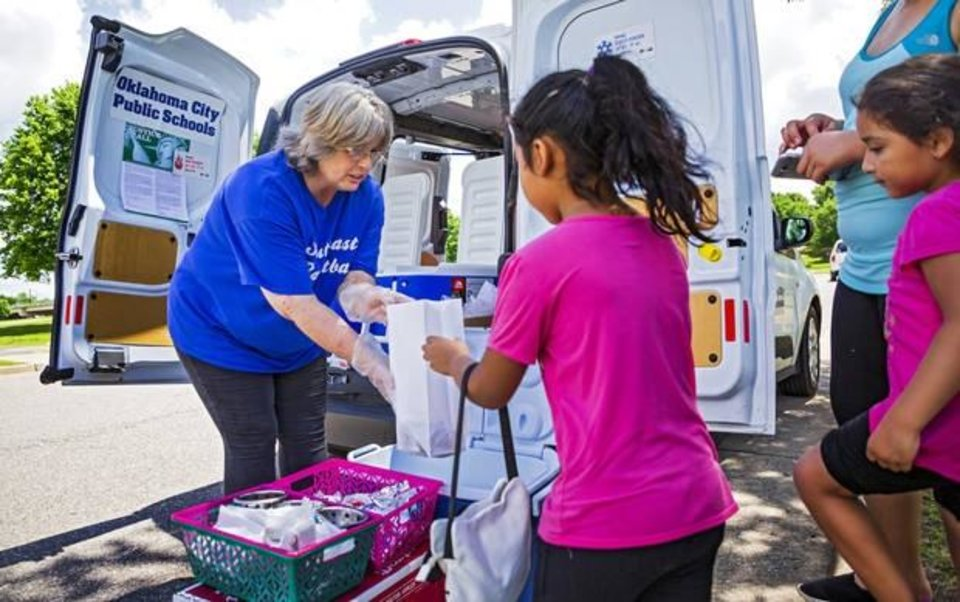 Photo -  Oklahoma City Public Schools kitchen supervisor Ramona Andruchow helps Yoselin Ramirez, 6, pick out items for her lunch during the Summer Feeding Program at Wiley Post Park in Oklahoma City on June 7, 2019. [Chris Landsberger/The Oklahoman]