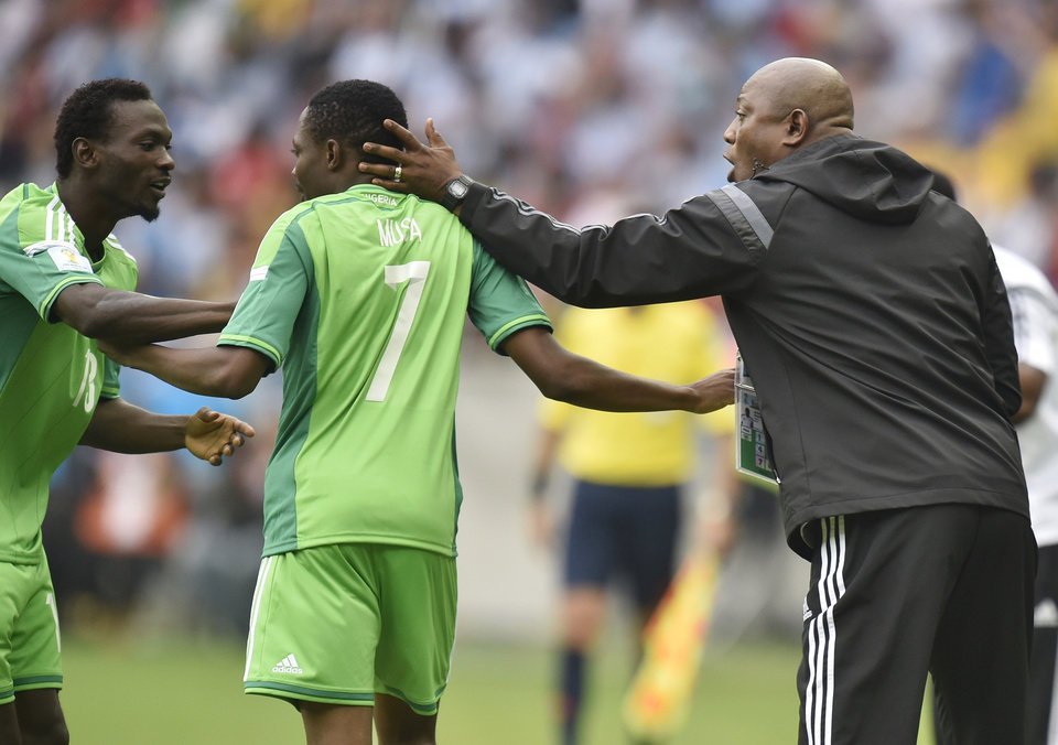 Photo - Nigeria's coach Stephen Keshi, right, and teammate Juwon Oshaniwa, left, congratulate Ahmed Musa after he scored his side's second goal during the group F World Cup soccer match against Argentina at the Estadio Beira-Rio in Porto Alegre, Brazil, Wednesday, June 25, 2014. (AP Photo/Martin Meissner)