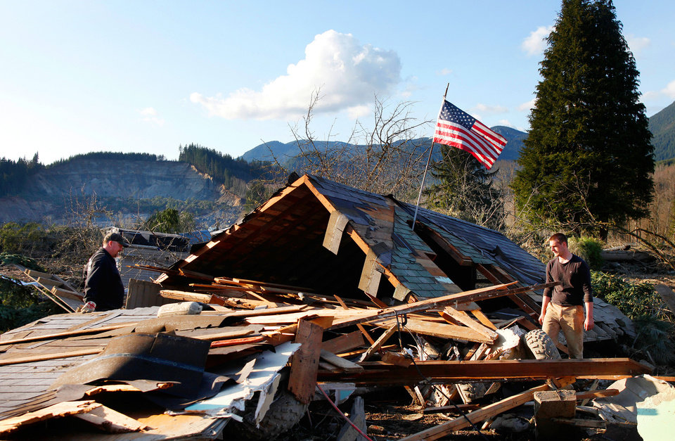 Photo - Brian Anderson, left,  and Coby Young search through the wreckage of a home belonging to the Kuntz family Sunday, March 23, 2014, near Oso, Wash. The entire Kuntz family was at a baseball game Saturday morning when a fatal mudslide swept through the area. The family returned Sunday to search through what remained. (AP Photo /The Herald, Genna Martin)