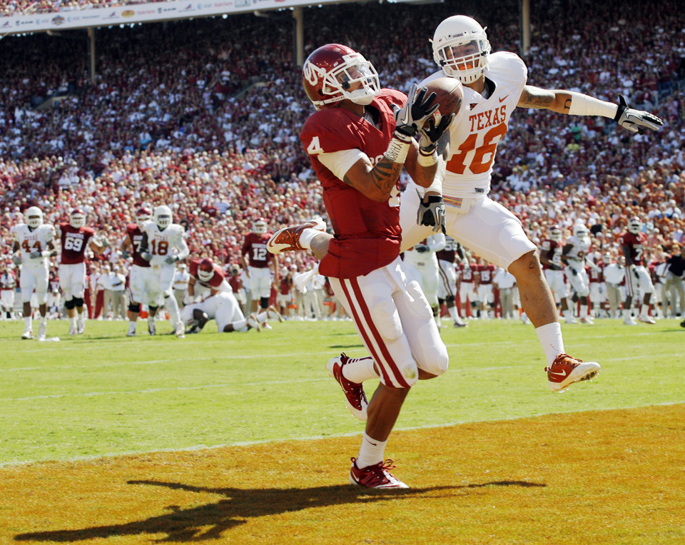 Photo - OU's Kenny Stills (4) catches a touchdown pass in the first quarter as Kenny Vaccaro (16) of Texas defends during the Red River Rivalry college football game between the University of Oklahoma Sooners (OU) and the University of Texas Longhorns (UT) at the Cotton Bowl on Saturday, Oct. 2, 2010, in Dallas, Texas. Photo by Nate Billings, The Oklahoman