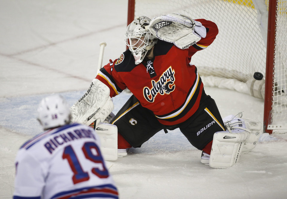 Photo - New York Rangers' Brad Richards, left, scores on Calgary Flames goalie Karri Ramo, from Finland, during the second period of an NHL hockey game in Calgary, Alberta, Friday, March 28, 2014. (AP Photo/The Canadian Press, Jeff McIntosh)
