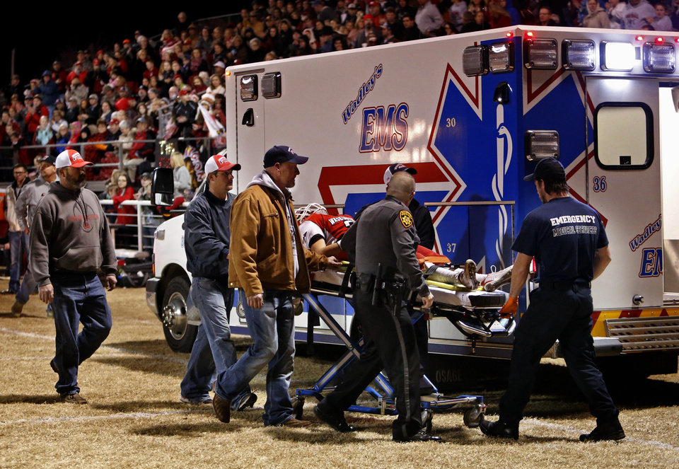 Photo - Washington player Brady Kulbeth is taken off the field on a backboard after a second quarter injury as the Nowata Ironmen play the Washington Warriors in high school football on Friday, Nov. 28, 2014 in Washington, Okla. Photo by Steve Sisney, The Oklahoman