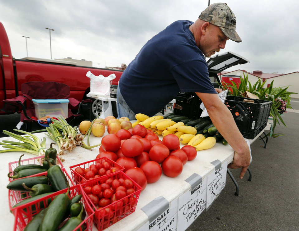 Randy Peters, with Dennis Farms of Blanchard, hangs price tags for vegetables Wednesday at the Norman Farm Market at the Cleveland County Fairgrounds. PHOTOS BY STEVE SISNEY, THE OKLAHOMAN