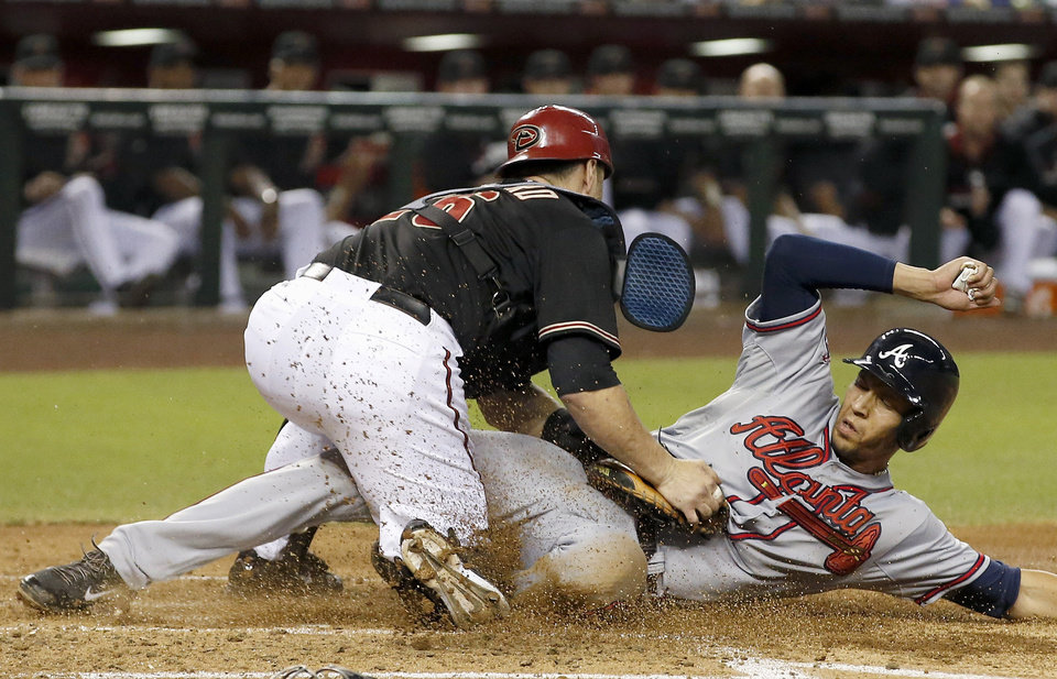 Photo - Atlanta Braves' Andrelton Simmons, right, scores ahead of the tag by Arizona Diamondbacks' Miguel Montero during the third inning of a baseball game Saturday, June 7, 2014, in Phoenix. (AP Photo/Ross D. Franklin)