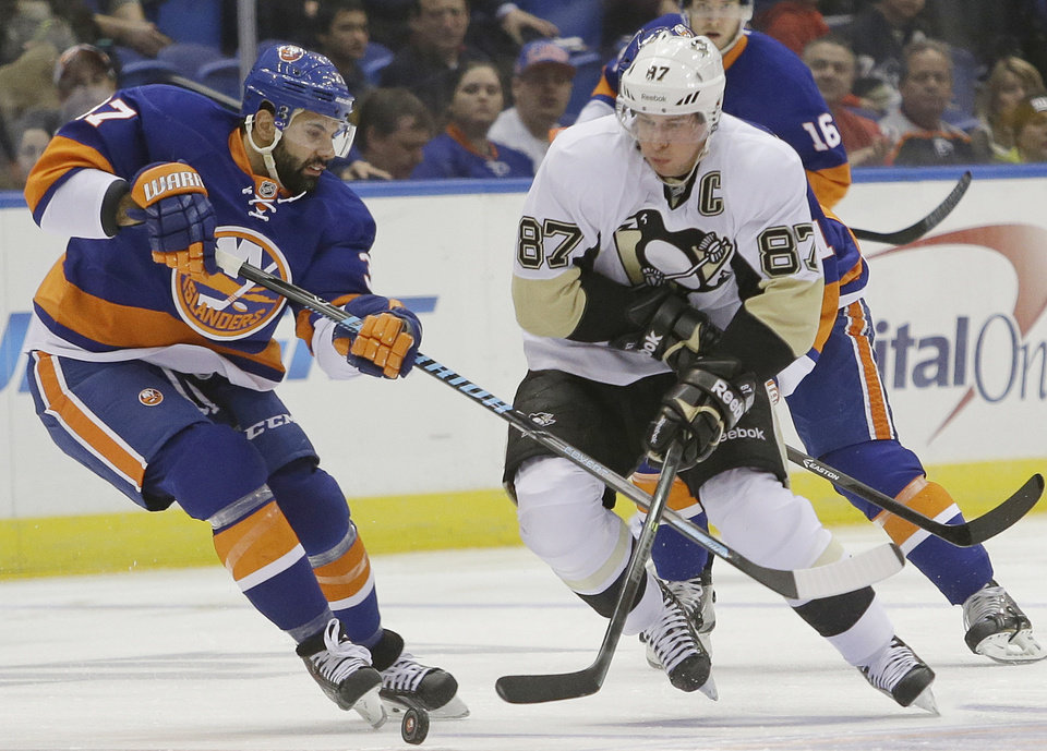 Photo - New York Islanders' Brian Strait (37) and Pittsburgh Penguins' Sidney Crosby (87) fight for control of the puck during the first period of an NHL hockey game, Thursday, Jan. 23, 2014, in Uniondale, N.Y. (AP Photo/Frank Franklin II)