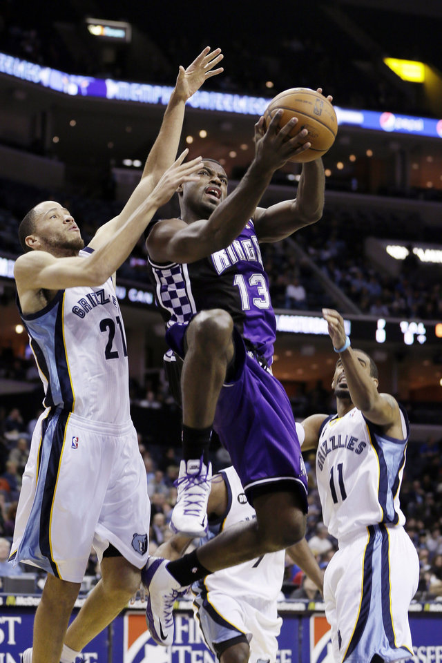Sacramento Kings' Tyreke Evans (13) goes to the basket between Memphis Grizzlies' Tayshaun Prince (21) and Mike Conley (11) during the first half of an NBA basketball game in Memphis, Tenn., Tuesday, Feb. 12, 2013. (AP Photo/Danny Johnston)