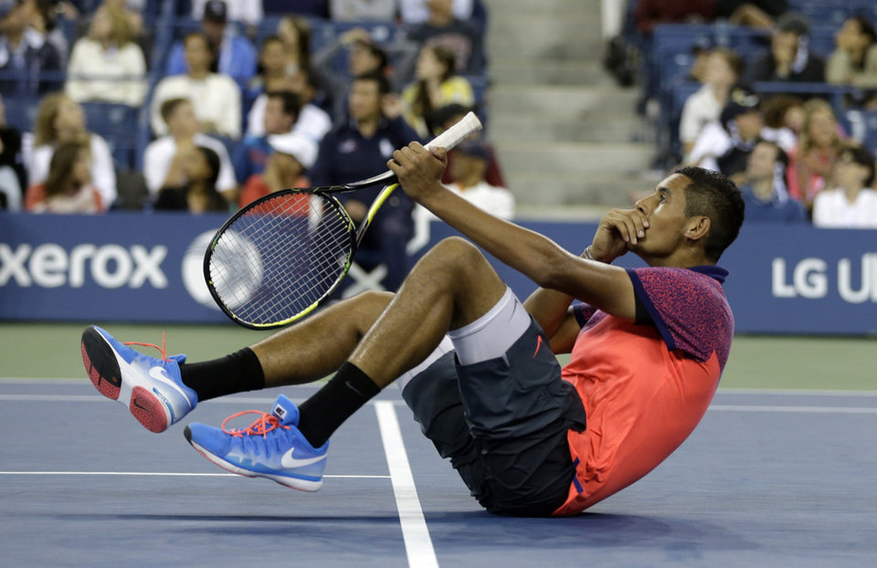 Photo - Nick Kyrgios, of Australia, falls back after watching a replay during his match against Tommy Robredo, of Spain,in the third round of the U.S. Open tennis tournament Saturday, Aug. 30, 2014, in New York. (AP Photo/Darron Cummings)