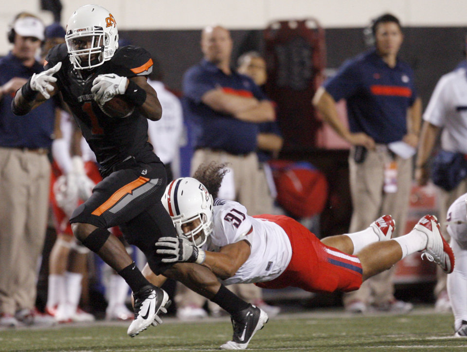 Photo - Oklahoma State's Joseph Randle (1) tries to shake Arizona's Sione Tuihalamaka (91) during their game Thursday in Stillwater. PHOTO BY SARAH PHIPPS, The Oklahoman