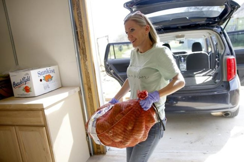 Photo - Kristen Hannam with Restore OKC carries a bag of potatoes to The Market at Restore OKC in Oklahoma City, Thursday, March 26, 2020. [Bryan Terry/The Oklahoman]