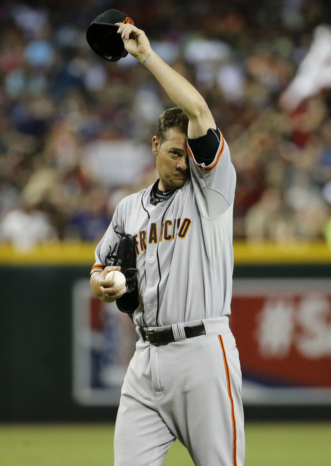Photo - San Francisco Giants pitcher Ryan Vogelsong wipes his face during the second inning of a baseball game against the Arizona Diamondbacks, Saturday, June 21, 2014, in Phoenix. (AP Photo/Matt York)