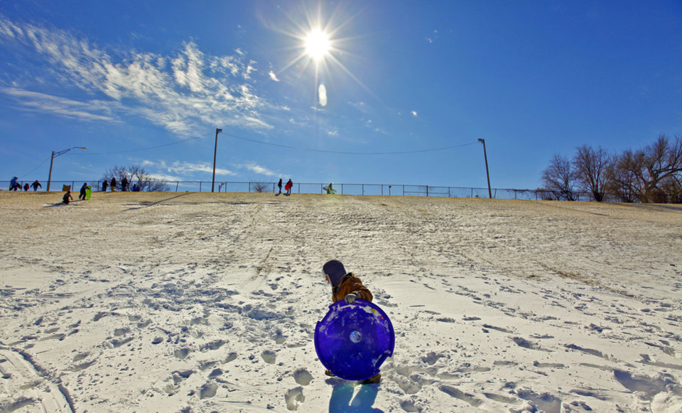 Photo - Christian Grassmann, 8, carries his sled as he makes the hard walk to the top of the hill to catch another ride down while enjoying the day out of school at Will Rogers Park on Wednesday, Feb. 2, 2011, Oklahoma City, Okla.   Photo by Chris Landsberger, The Oklahoman