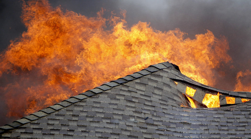 Photo - Fire burns a roof on a house in the Oakwood East Royale neighborhood in Midwest City, Thursday, April 9, 2009. Photo by Bryan Terry, The Oklahoman