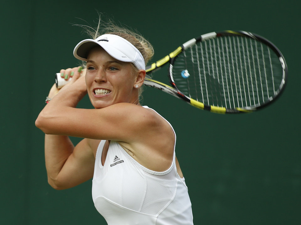 Photo - Caroline Wozniacki of Denmark watches a return to Shahar Peer of Israel during their first round match at the All England Lawn Tennis Championships in Wimbledon, London,  Monday, June  23, 2014. (AP Photo/Alastair Grant)