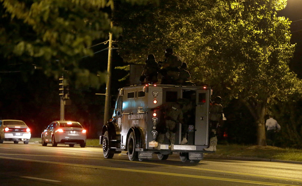 Photo - An armored personnel carrier speeds down the street Wednesday, Aug. 13, 2014, in Ferguson, Mo.  Protests in the St. Louis suburb rocked by racial unrest since a white police officer shot an unarmed black teenager to death turned violent Wednesday night, with people lobbing molotov cocktails at police who responded with smoke bombs and tear gas to disperse the crowd.  (AP Photo/Jeff Roberson)