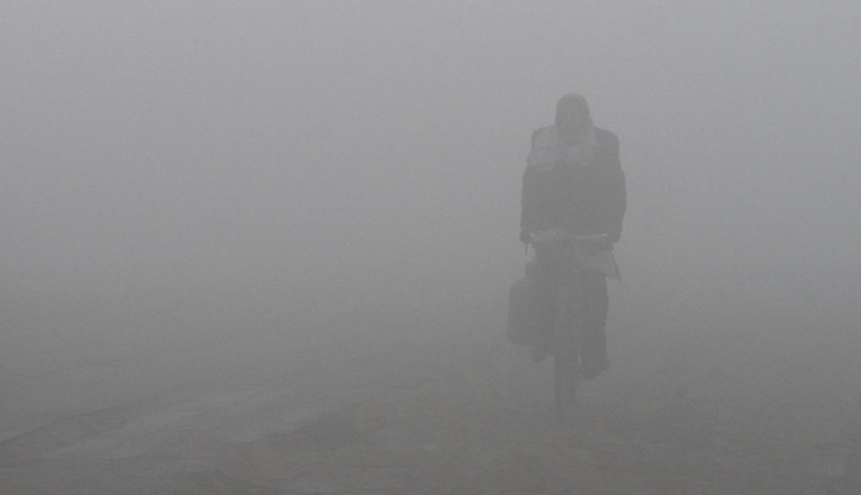 An Indian cyclist rides on the banks of the Ganges River on a cold and foggy morning in Allahabad, India, Sunday, Dec. 30, 2012. North India continues to face extreme weather conditions with dense fog affecting flights and trains. (AP Photo/Rajesh Kumar Singh)