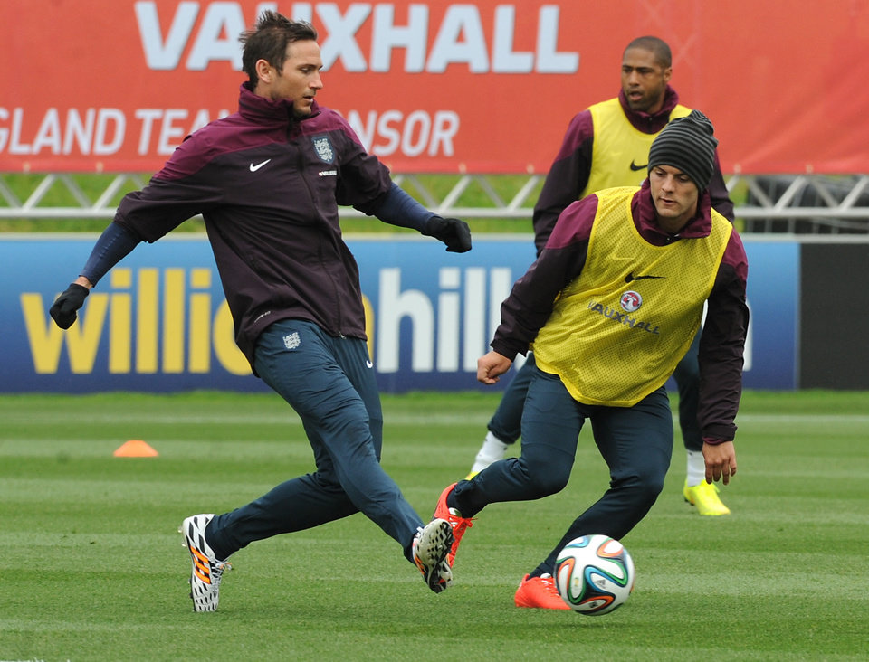 Photo - England national soccer team players Frank Lampard, left, and Jack Wilshere kick a ball during a training session at George's Park in Burton on Trent, England, Tuesday, May 27, 2014. England play an international friendly soccer match against Peru at Wembley on Friday. (AP Photo/Rui Vieira)