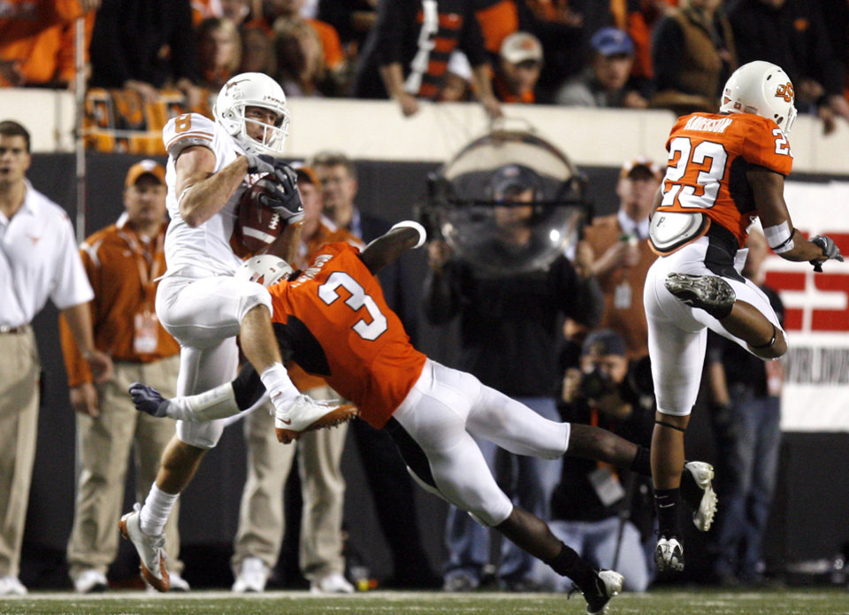 Photo - Texas' Jordan Shipley (8) catches a pass as OSU's Victor Johnson (3) and Terrance Anderson (23) defend during the college football game between the Oklahoma State University Cowboys (OSU) and the University of Texas Longhorns (UT) at Boone Pickens Stadium in Stillwater, Okla., Saturday, Oct. 31, 2009. Photo by Sarah Phipps, The Oklahoman