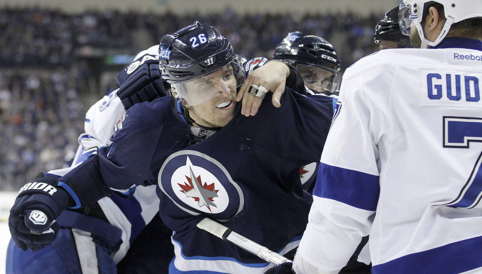 Photo - Winnipeg Jets' Blake Wheeler (26) is held back from Tampa Bay Lightning's Radko Gudas (7) during the second period of an NHL hockey game Tuesday, Jan. 7, 2014, in Winnipeg, Manitoba. (AP Photo/The Canadian Press, Trevor Hagan)