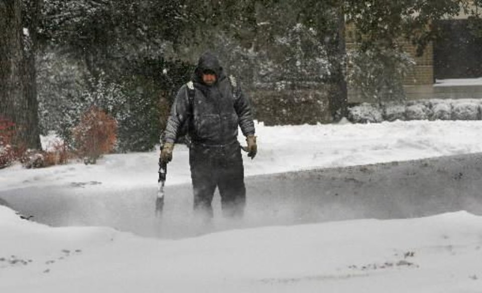 Photo - City employee Philip Brooks uses a leaf blower to clear snow near the Municipal Complex as the second round of show in a week moved into the area on Wednesday, February 9, 2011, in Norman, Okla. Photo by Steve Sisney