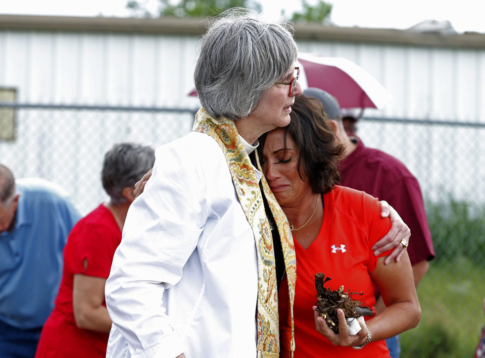 Photo - The Rev. Susan Joplin, a canon at St. Paul's Episcopal Cathedral, hugs Michelle Ratliff of Moore after she honored her horses Sawyer and Biscuit during a memorial service Saturday at the Orr Family Farm, 14400 S Western, for animals who died in recent tornadoes.   SARAH PHIPPS - SARAH PHIPPS