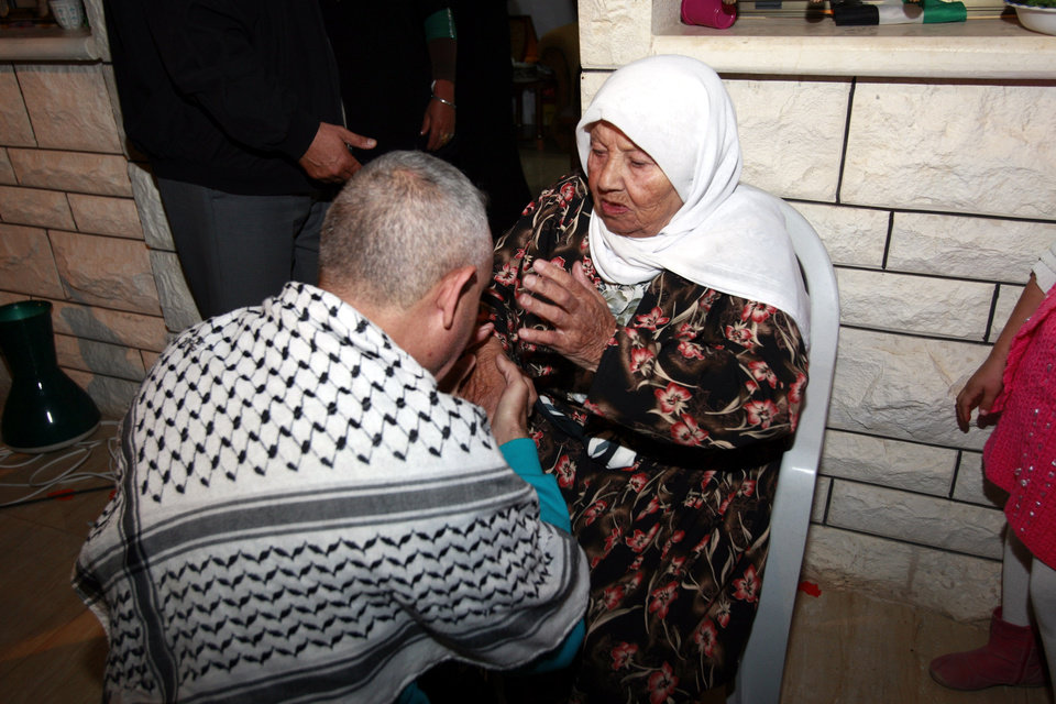 Photo - Released Palestinian prisoner Hazza Saadi kisses his mother upon returning to his home in the West Bank refugee camp of Jenin after his release Wednesday, Oct. 30, 2013. Israel released 26 Palestinian prisoners, as part of a U.S.-brokered agreement that restarted peace talks with the Palestinians over the summer. It is the second of four planned releases of the longest-serving Palestinian prisoners held by Israel in the coming months. (AP Photo/Mohammed Ballas)