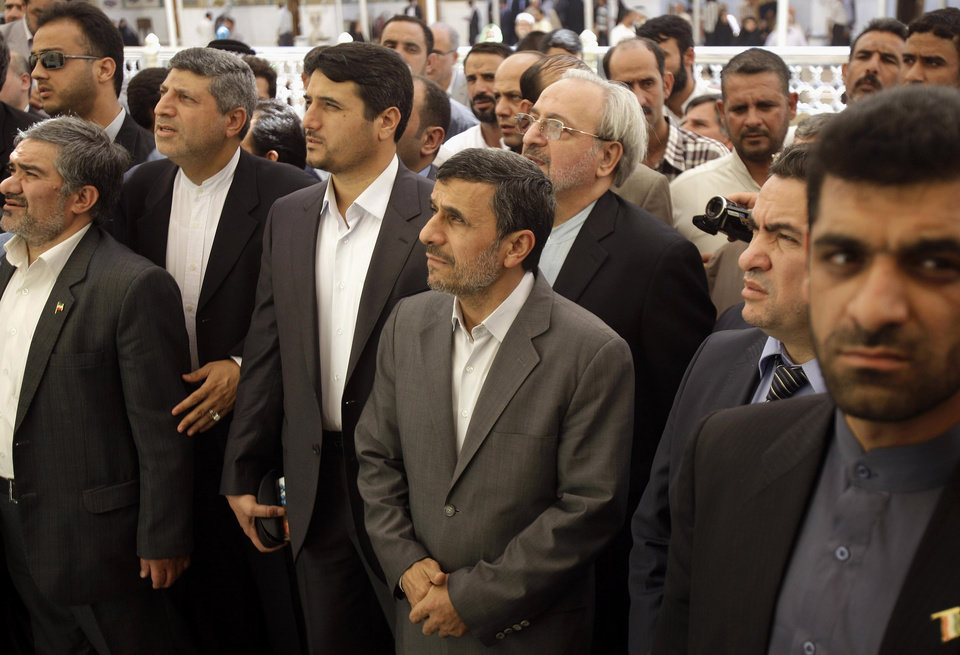 Photo - Iranian President Mahmoud Ahmadinejad, center, visits Imam Ali shrine in Najaf, Iraq, Friday, July 19, 2013. Ahmadinejad is in southern Iraq to visit two of the holiest cities for Shiite Muslims amid tight security on the second day of his two-day visit to the country. The outgoing Iranian president waved to worshippers and smiled on Friday morning as he entered the Imam Ali shrine in Najaf, a city 160 kilometers (100 miles) south of Baghdad. (AP Photo/Karim Kadim, Pool)