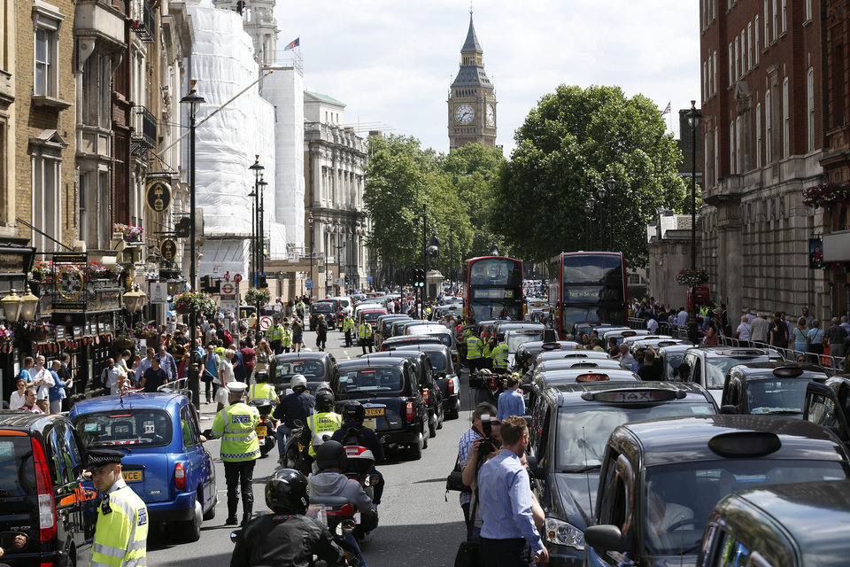 Photo - Roads are snarled in London as Taxi drivers stop their black cabs, blocking the street to protest over new technology they say endangers passengers, London, Wednesday, June 11, 2014.  The strike action by taxi drivers hit many European cities, Wednesday, sparked by fears about the growing upheaval in the travel and transport industry, largely due to digital technologies. Big Ben's clock tower back centre. (AP Photo/Sang Tan)