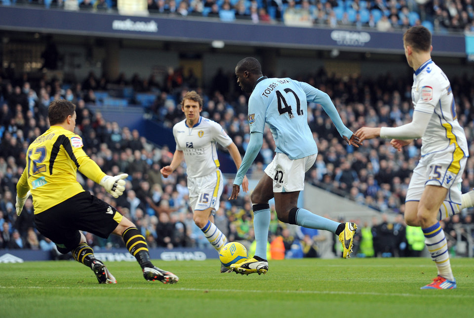 Photo - Manchester City's Yaya Toure, centre, slips past Leeds United goal keeper Jamie Ashdown, left, to score the first goal of the game for his side during their English FA Cup fifth round soccer match against Leeds United at the Etihad Stadium in Manchester, England, Sunday Feb. 17, 2013. (AP Photo/Clint Hughes)
