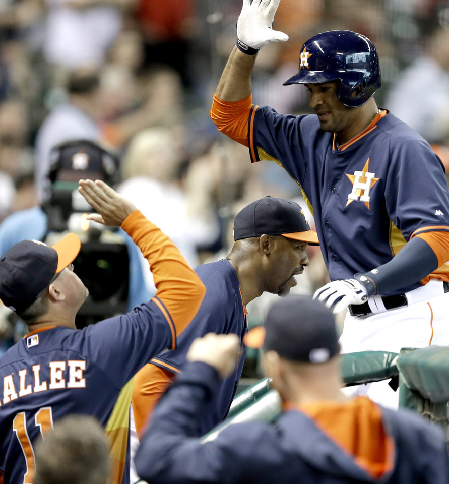 Photo - Houston Astros' Jesus Guzman, right, is welcomed back to the dugout by hitting coach John Mallee (11) after hitting a solo home run against the Los Angeles Angels in the fourth inning of a baseball game on Sunday, April 6, 2014, in Houston. (AP Photo/Pat Sullivan)