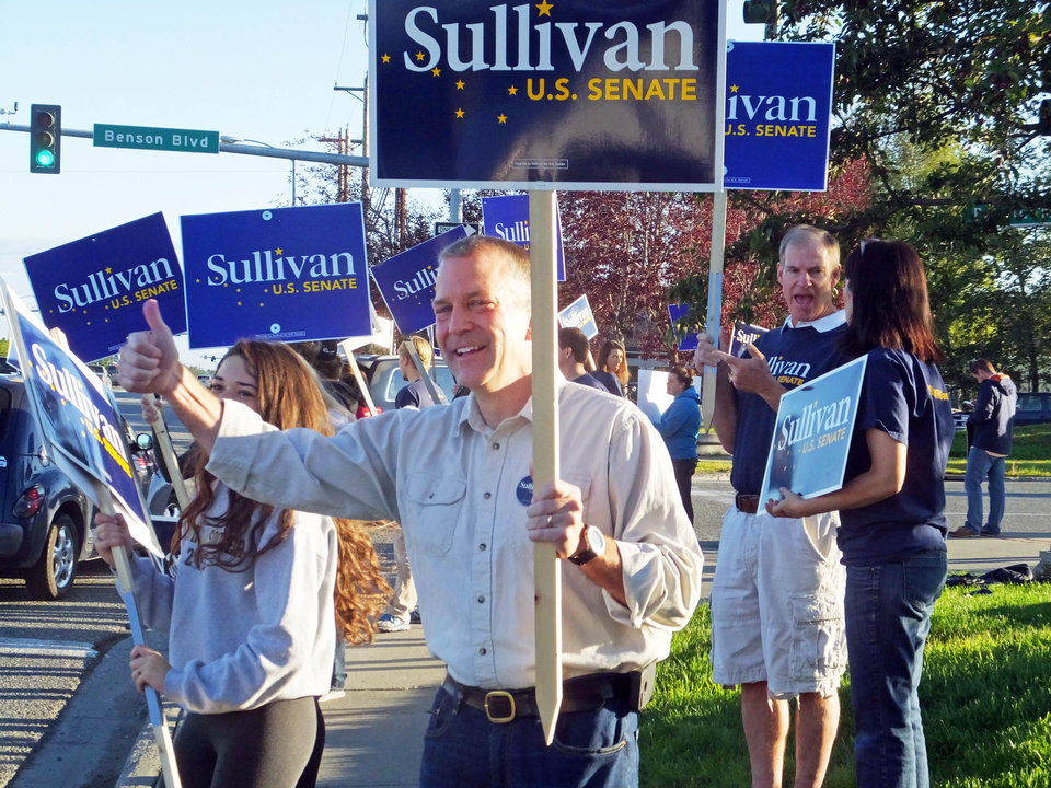 Photo - Dan Sullivan, candidate for the Republican candidate for election to the U.S. Senate, waves signs along a busy street on the morning of Alaska's primary election Tuesday, Aug. 19, 2014, in Anchorage, Alaska. (AP Photo/Becky Bohrer)