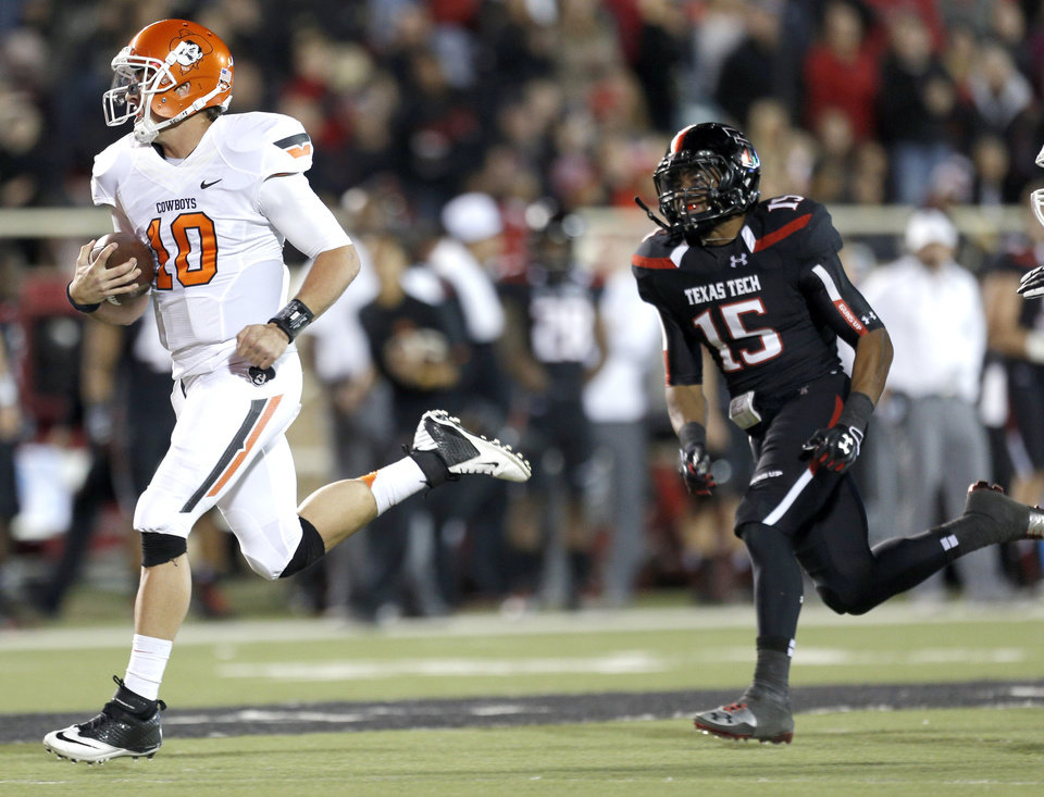 Oklahoma State \'s Clint Chelf (10) scores a touchdown as Texas Tech\'s Keenon Ward (15) chases him down during the college football game between the Oklahoma State Cowboys (OSU) and the Texas Tech Red Raiders (TTU) at Jones AT&T Stadium in Lubbock, Texas, Saturday, Nov. 2, 2013. Photo by Sarah Phipps, The Oklahoman