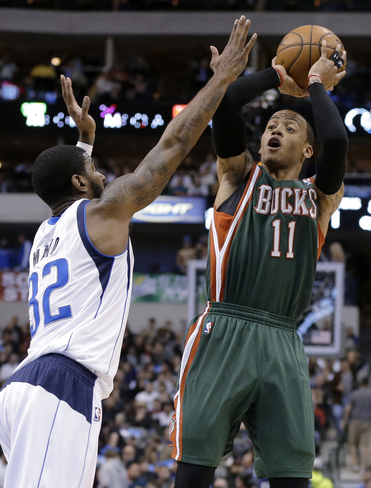 Dallas Mavericks' O.J. Mayo (32) defends as Milwaukee Bucks' Monta Ellis (11) shoots during the first half of an NBA basketball game Tuesday, Feb. 26, 2013, in Dallas. (AP Photo/Tony Gutierrez)