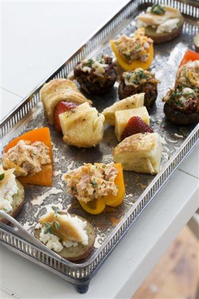 Photo - In this image taken on April 22, 2013, front to back, smoked schmeared potatoes, stuffed baby bell peppers, strawberry croissant skewers, and chorizo hash stuffed mushroom caps, are shown served on a tray in Concord, N.H. (AP Photo/Matthew Mead)