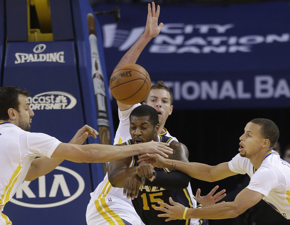 Photo - Utah Jazz power forward Derrick Favors (15) passes as he is defended by Golden State Warriors center Andrew Bogut, from left, power forward David Lee and shooting guard Stephen Curry during the first quarter of an NBA basketball game in Oakland, Calif., Saturday, Nov. 16, 2013. (AP Photo/Jeff Chiu)