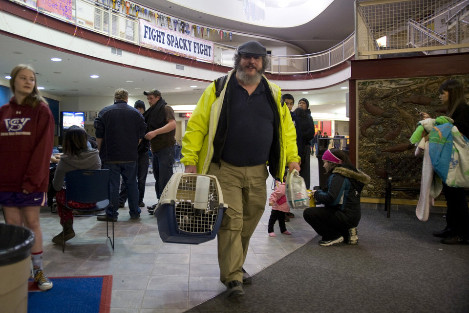 Photo - Charles Bingham heads back home with his cats after a tsunami warning was canceled early Saturday, Jan. 5, 2013, in Sitka, Alaska, following a magnitude 7.5 earthquake. (AP Photo/Daily Sitka Sentinel, James Poulson)