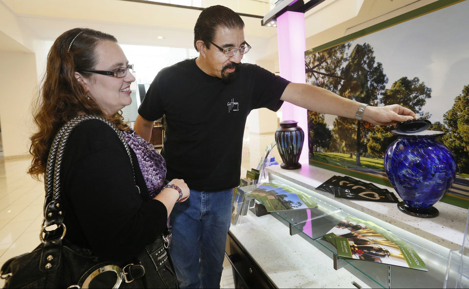 Photo - In this photo taken Thursday, Jan. 30, 2014, Mark Sanchez and his wife Lea' Anne Sanchez look at a Dodger's theme cremation urn at the Forest Lawn stand at the Glendale Galleria mall in Glendale, Calif. Forest Lawn, famous as the final resting place for everyone from Al Jolson to Michael Jackson, has begun staffing outlets at shopping malls, reasoning that planning for death, either for a loved one or yourself, might not be quite as intimidating for some people if it takes place in a lively, happy place like a mall rather than the more somber confines of a cremation home. (AP Photo/Damian Dovarganes)