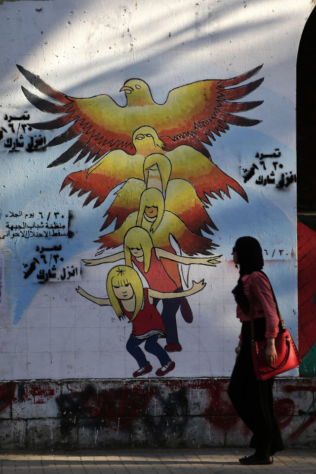 Photo - An Egyptian woman walks past graffiti on a wall with Arabic writing that reads,
